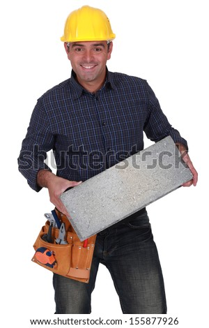 Cheerful builder with a concrete block - stock photo