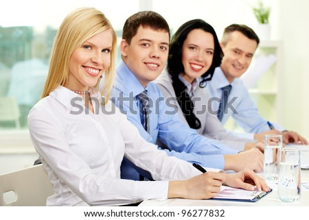 Cheerful business colleagues sitting at table and smiling at camera