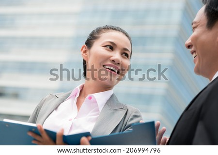 Cheerful business lady talking to her colleague - stock photo