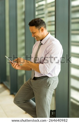 cheerful business man using smart phone in modern office - stock photo