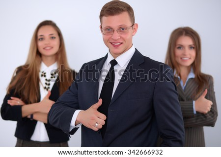 Cheerful business man  with colleagues in the background, thumbs up - stock photo