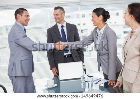 Cheerful business people meeting and shaking hands in bright office - stock photo
