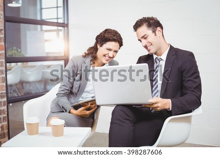 Cheerful business people using technology while discussing at office - stock photo