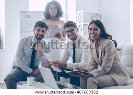 Cheerful business team. Group of four young people looking at camera with smile while sitting on the couch at office   - stock photo