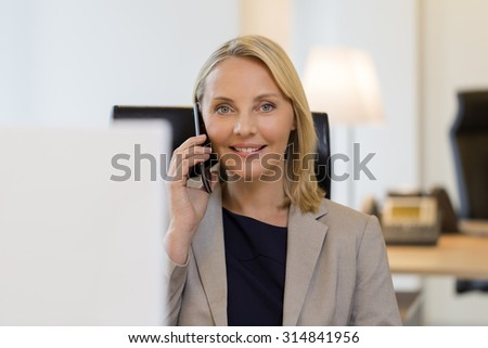 Cheerful business woman on cell phone at office - stock photo