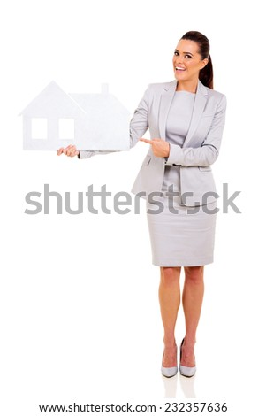 cheerful business woman pointing white paper house - stock photo