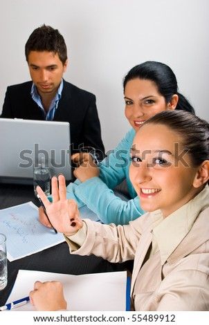 Cheerful business woman showing okay sign gesture hand at meeting - stock photo