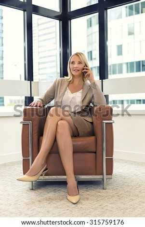 Cheerful business woman sitting in a chair. on mobile phone in modern office - stock photo