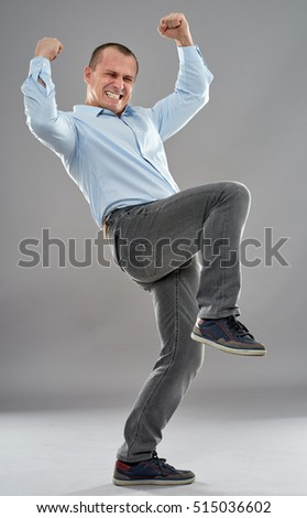Cheerful businessman celebrating success, full body on gray background
