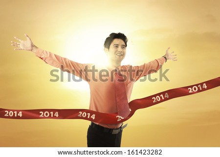Cheerful businessman crossing the finish line of racing track under sunset - stock photo