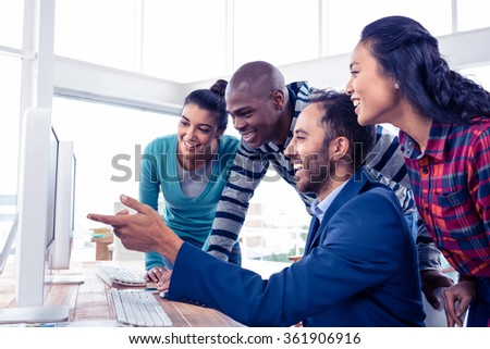 Cheerful businessman giving training to team over computer in creative office - stock photo
