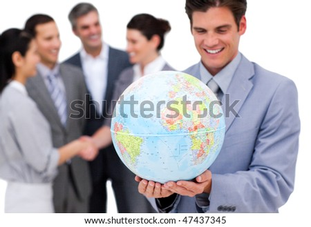 Cheerful businessman holding a globe in front of his team against a white background - stock photo