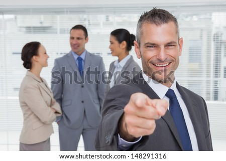 Cheerful businessman in bright office pointing at camera with colleagues on background - stock photo
