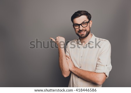 Cheerful businessman in glasses pointing away on gray background
