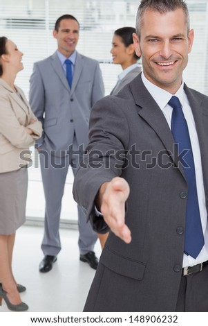 Cheerful businessman introducing himself holding out his hand in bright office - stock photo