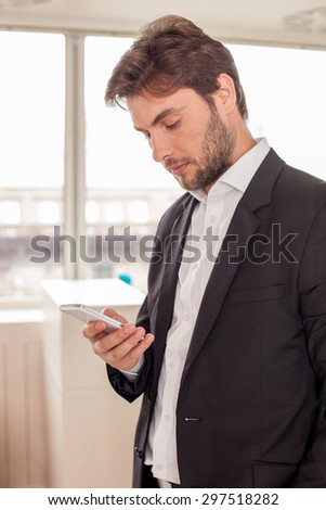 Cheerful businessman is holding a mobile phone and messaging to his client. He is looking at it with concentration - stock photo