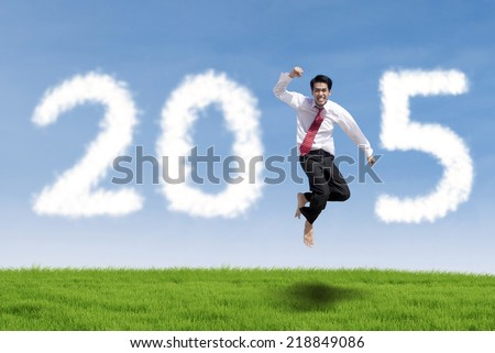Cheerful businessman jumping on meadow with cloud forming number 2015 - stock photo