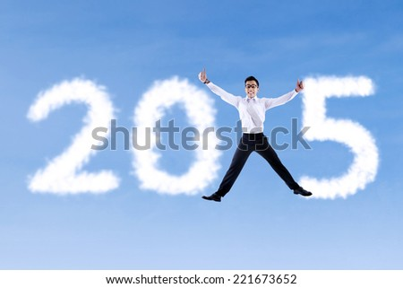 Cheerful businessman jumping on the sky and forming number 2015 - stock photo