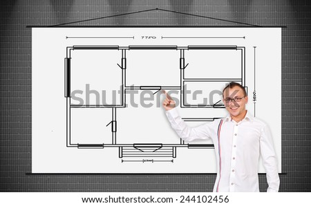 cheerful businessman pointing to a poster with drawing blueprint - stock photo