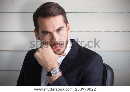 Cheerful businessman posing with hand on chin against painted blue wooden planks - stock photo