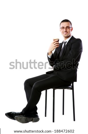 Cheerful businessman sitting with cup of coffee over white background - stock photo