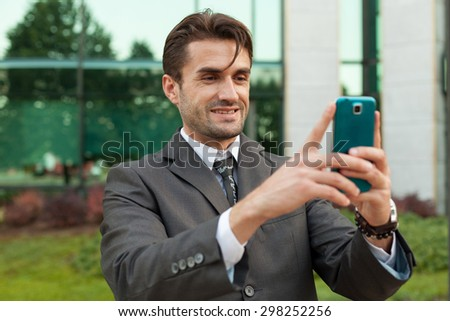 Cheerful businessman taking selfie