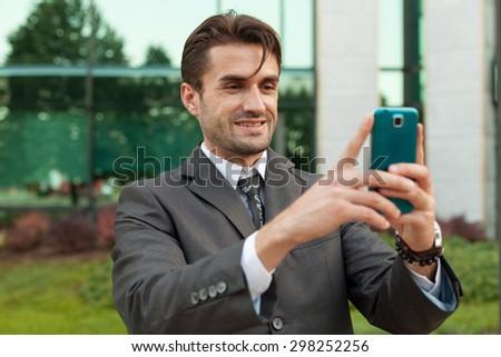 Cheerful businessman taking selfie - stock photo