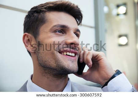 Cheerful businessman talking on the phone outdoors