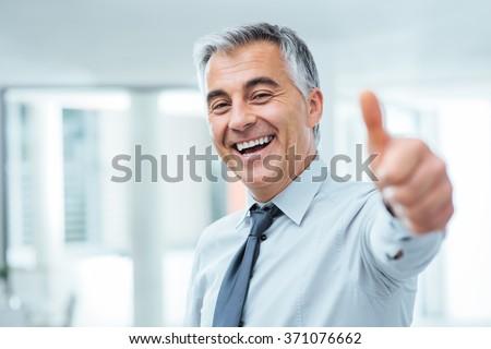 Cheerful businessman thumbs up posing and smiling at camera - stock photo