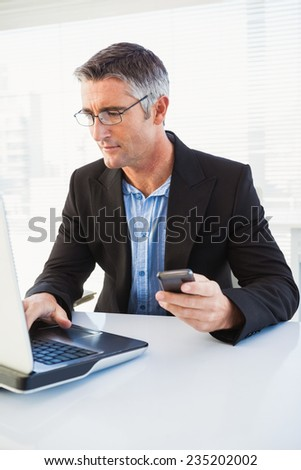 Cheerful businessman using laptop and holding smartphone in his office