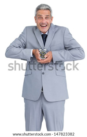 Cheerful businessman with alarm clock in both hands on white background - stock photo