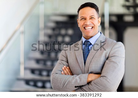 cheerful businessman with arms folded in modern office - stock photo
