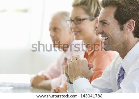 Cheerful businessman with colleagues in conference room - stock photo