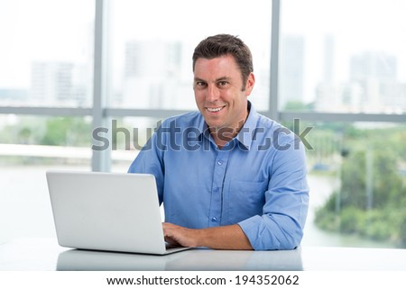 Cheerful businessman working on his laptop in the office - stock photo