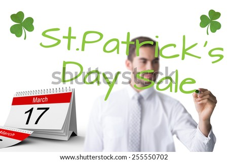 Cheerful businessman writing with marker against shamrock - stock photo