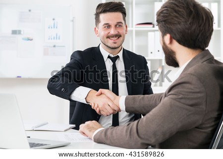 Cheerful businessmen shaking hands at modern office desk with laptop and other items. Businesspeople closing business deal - stock photo