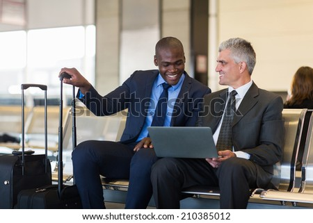 cheerful businessmen using laptop computer at airport - stock photo
