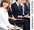 Cheerful businesspeople at business meeting, seminar, conference or training - stock photo