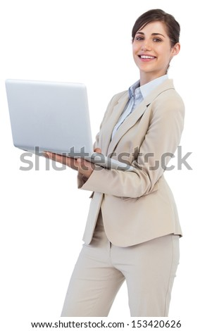Cheerful businesswoman against white background holding laptop - stock photo