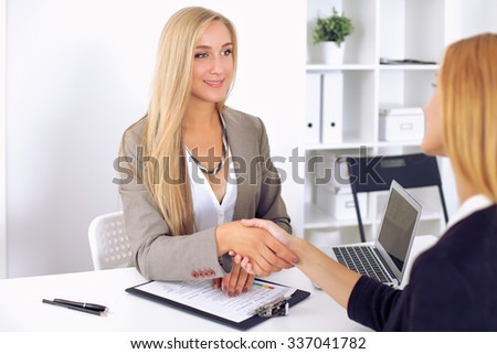 Cheerful  businesswoman and client handshaking, sitting at the table