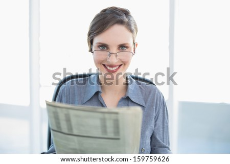 Cheerful businesswoman holding newspaper sitting at her desk looking at camera - stock photo