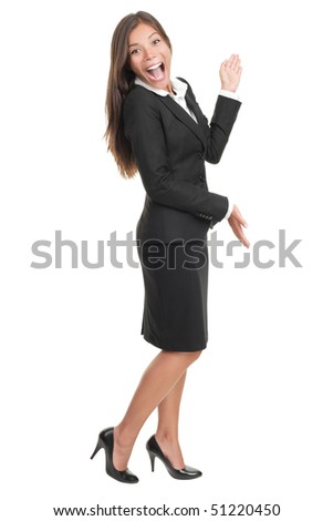 Cheerful businesswoman in black skirt suit presenting and showing copy space. Happy smiling full body portrait of a beautiful Asian / Caucasian young business woman model cut out on white background. - stock photo
