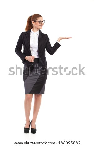 Cheerful businesswoman in black suit raising hand ans showing product. Full length studio shot isolated on white. - stock photo