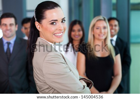 cheerful businesswoman in office with co-workers on background