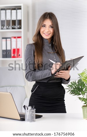 Cheerful Businesswoman in the office, standing with documents. Looking at camera.