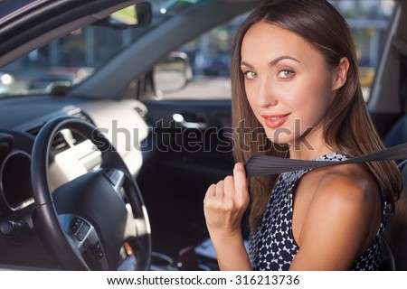 Cheerful businesswoman is fastening the seat belt. She is sitting at the steering wheel of her car. The lady is smiling and looking at the camera with joy - stock photo