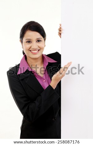Cheerful businesswoman pointing at billboard - stock photo