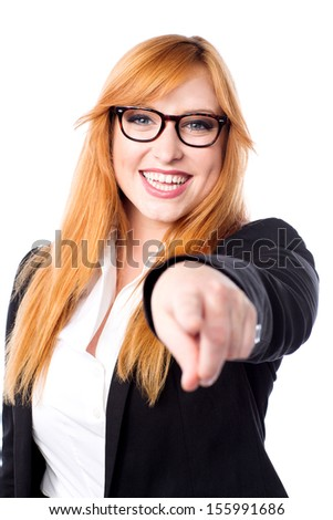 Cheerful businesswoman pointing towards camera