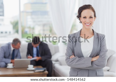 Cheerful businesswoman posing while her colleagues are working in bright office - stock photo