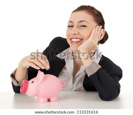 cheerful businesswoman putting coin to piggybank, white background - stock photo
